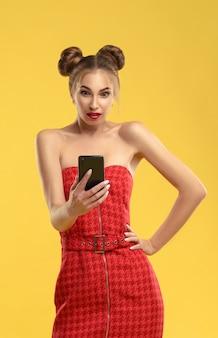 Garota de vestido vermelho com pães de cabelo surpreso e olhando para smartphone na parede amarela