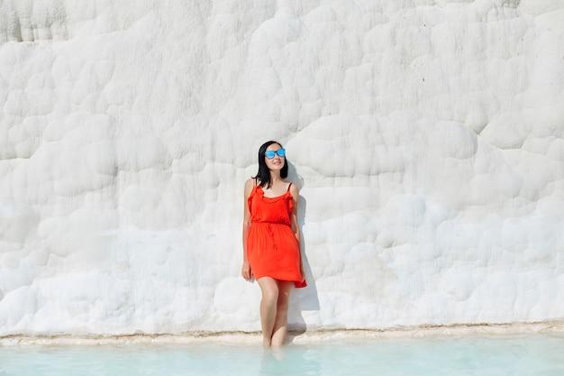 Garota de vestido vermelho em travertinos brancos, água