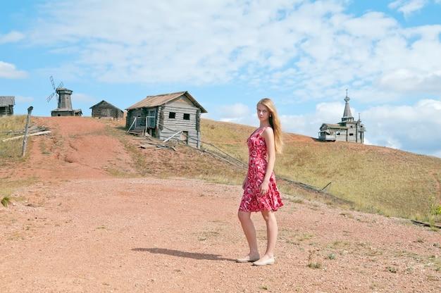 Garota de vestido vermelho em uma rua de aldeia
