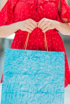 Garota de vestido vermelho, segurando o saco de compras