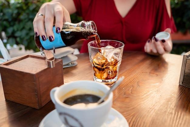 Garota de vestido vermelho serve uma bebida cola café gelado
