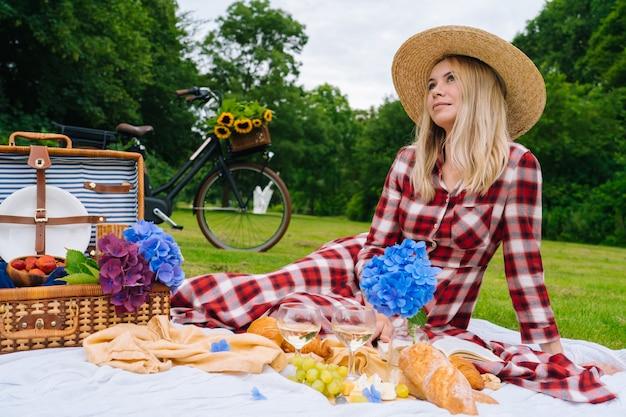 Garota de vestido xadrez vermelho e chapéu, sentado no livro de leitura de manta de piquenique de malha branca e bebendo vinho. piquenique de verão em dia ensolarado com pão, fruta, flores de hortênsia buquê. foco seletivo