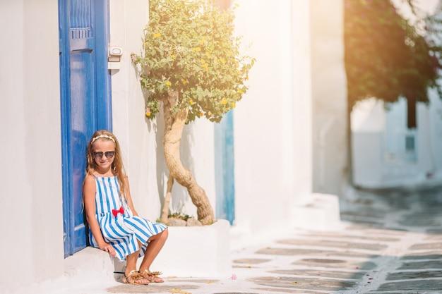 Garota de vestidos brancos se divertindo ao ar livre nas ruas de mykonos