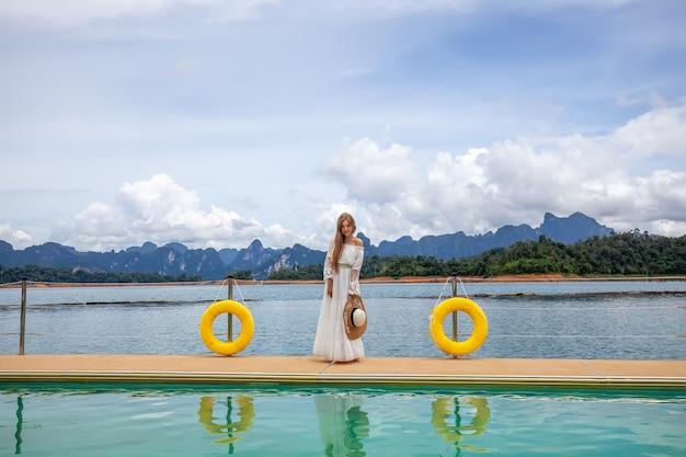 Garota de viagem feliz no cais de madeira com a floresta tropical do lago e as montanhas