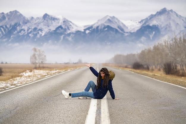 Garota de viagem para montanhas sentada na estrada mostrando a montanha