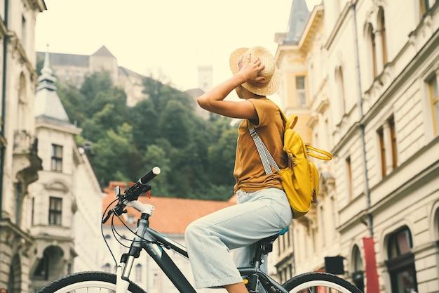 Garota de viagem pela europa com mochila e bicicleta urbana em uma rua antiga no centro histórico de ljubljana