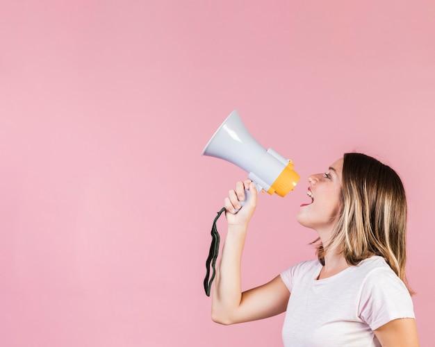 Garota de visão lateral falando em um megafone