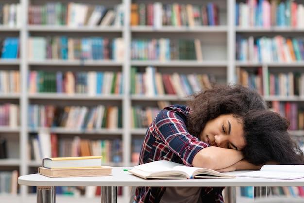 Garota de vista frontal adormeceu na biblioteca enquanto estudava