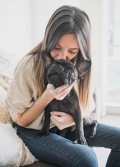 Garota de vista frontal beijando seu cachorrinho
