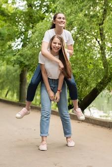 Garota de vista frontal carregando sua amiga nas costas