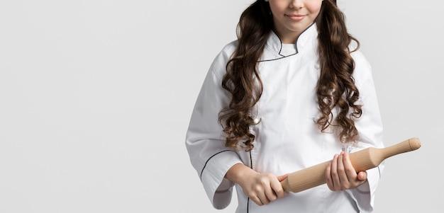 Garota de vista frontal com cabelo encaracolado, segurando o rolo