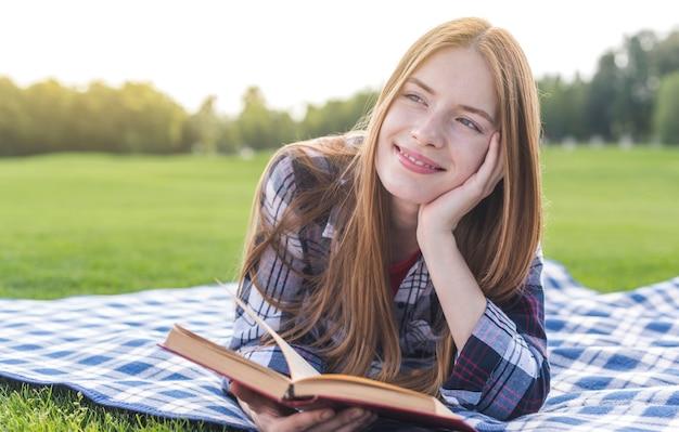 Garota de vista frontal com um livro a desviar o olhar