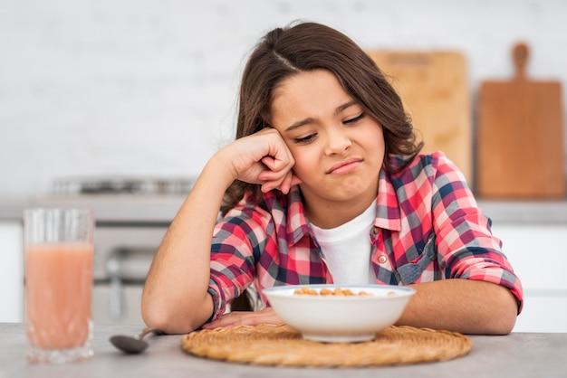 Garota de vista frontal infeliz com café da manhã