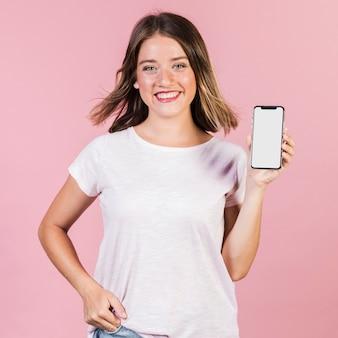 Garota de vista frontal mostrando seu telefone
