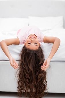 Garota de vista frontal na borda da cama com a cabeça pendurada