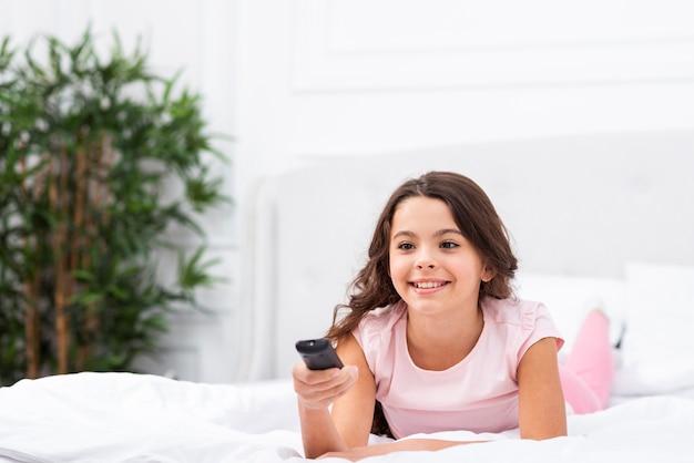 Garota de vista frontal na cama usando o controle remoto da tv