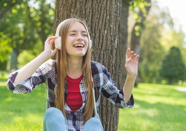 Garota de vista frontal, ouvindo música ao ar livre