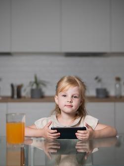 Garota de vista frontal segurando móvel em casa