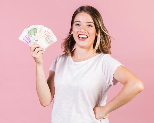 Garota de vista frontal, segurando o dinheiro
