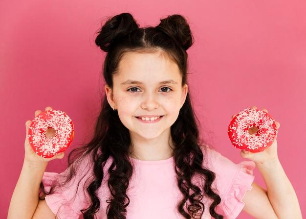 Garota de vista frontal segurando rosquinhas nas mãos dela