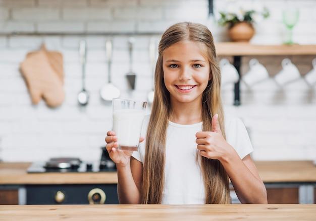 Garota de vista frontal, segurando um copo de leite