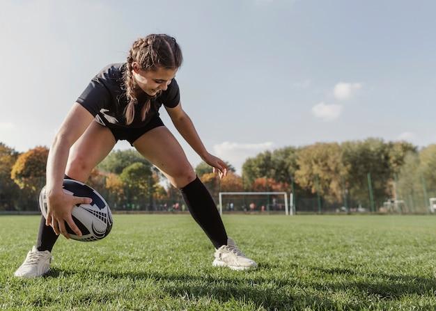 Garota de vista frontal, segurando uma bola com espaço de cópia