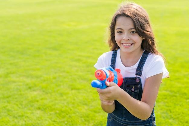 Garota de vista frontal segurando uma pistola de água