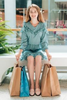 Garota de vista frontal sentado com sacolas de compras