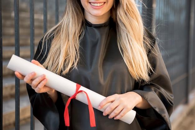 Garota de vista frontal sorrindo segurando seu certificado