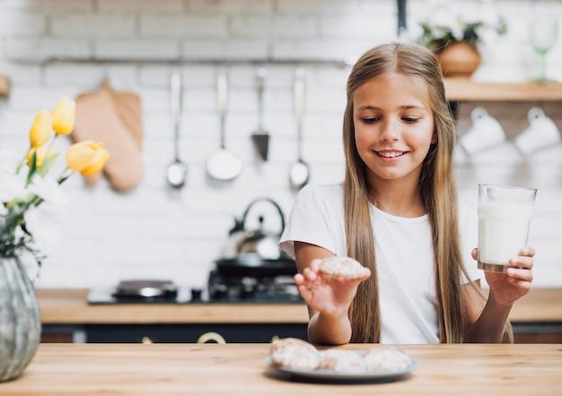 Garota de vista frontal tomando um biscoito e segurando um copo de leite