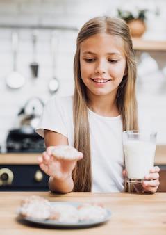 Garota de vista frontal tomando um biscoito