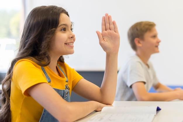 Garota de vista lateral com a mão levantada