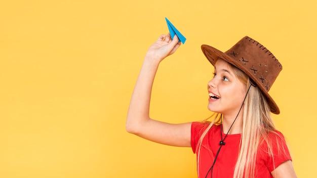 Garota de vista lateral com avião de papel
