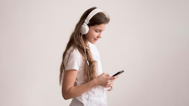 Garota de vista lateral com fones de ouvido