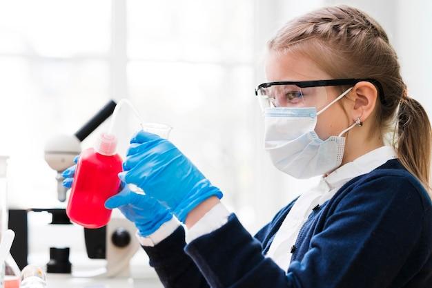 Garota de vista lateral com máscara cirúrgica
