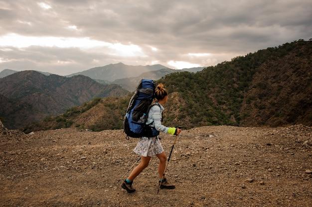 Garota de vista lateral com mochila e bengalas andando na estrada de terra