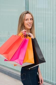 Garota de vista lateral com sacos de compras, olhando para longe