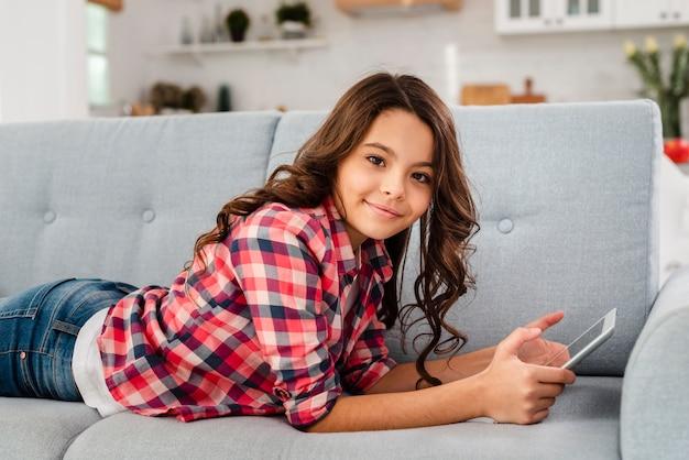 Garota de vista lateral em casa deitado no sofá