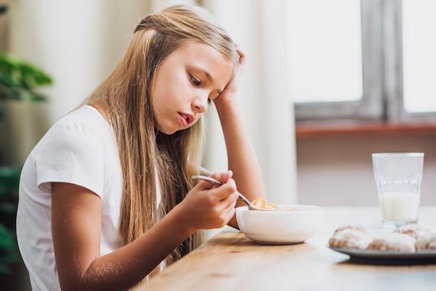 Garota de vista lateral tomando uma colher de cereal