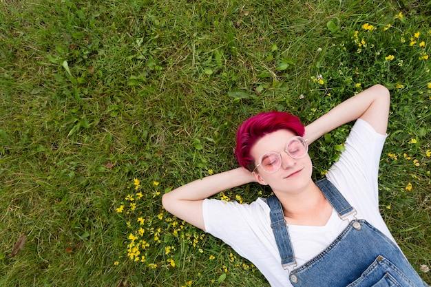 Garota de vista superior, deitado na grama