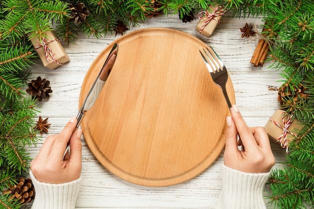 Garota de vista superior mantém garfo e faca na mão e está pronta para comer