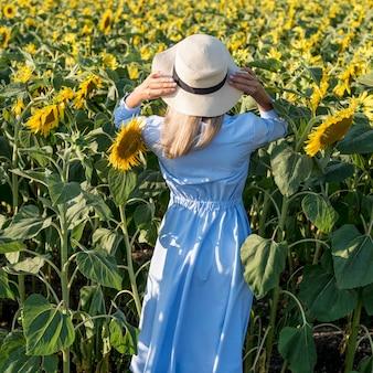 Garota de vista traseira caminhando em um campo com flores do sol