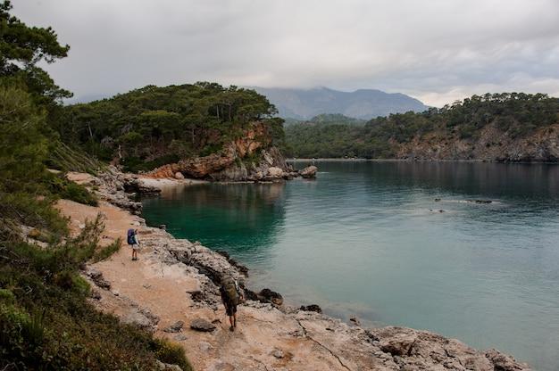Garota de vista traseira com mochila e bengalas andando no litoral rochoso