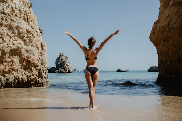 Garota de vista traseira em traje de banho com nádegas sensuais fica na grande pedra na praia durante o pôr do sol.