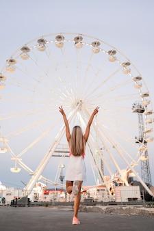 Garota de vista traseira no parque de diversões