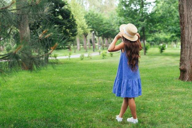 Garota de vista traseira posando ao ar livre