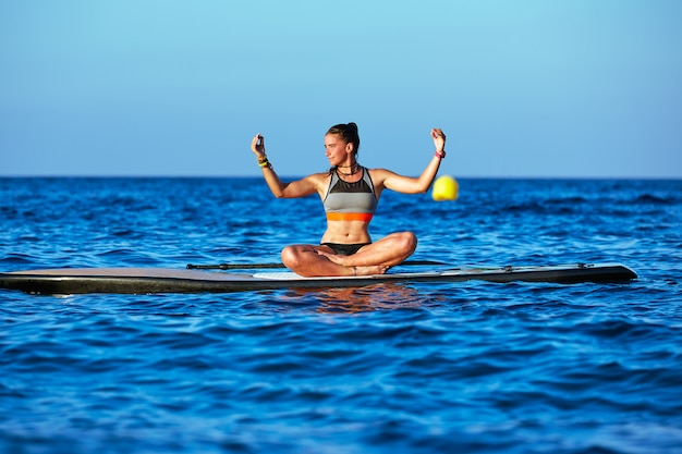 Garota de yoga sobre sup stand up surf board