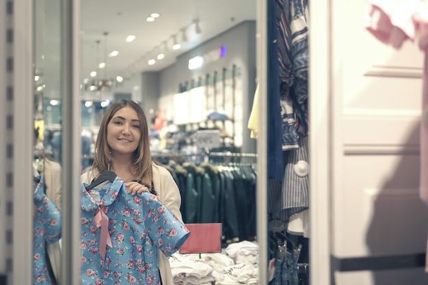 Garota de yong escolhendo roupas e olhando para o espelho no shopping ou loja de roupas. conceito de compras, moda, estilo e pessoas.