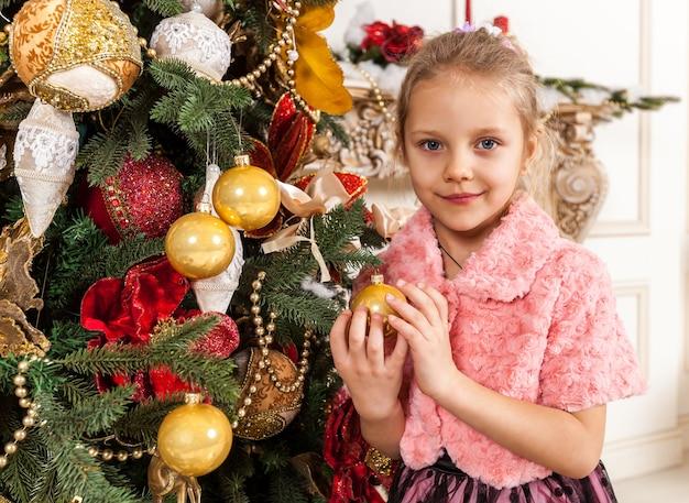 Garota decora uma árvore de natal, uma garota de natal segurando um brinquedo nas mãos de