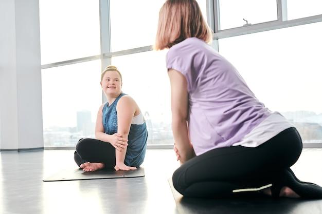 Garota deficiente feliz vestindo roupas esportivas, olhando para a amiga enquanto ambas estão sentadas em colchonetes e discutindo os exercícios que vão fazer